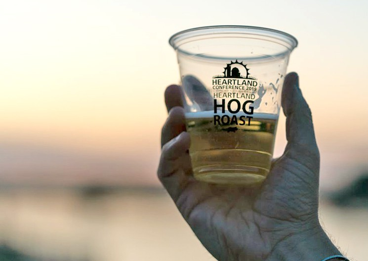 a hand holding a heartland hog roast cup in cheers with sunset in the background